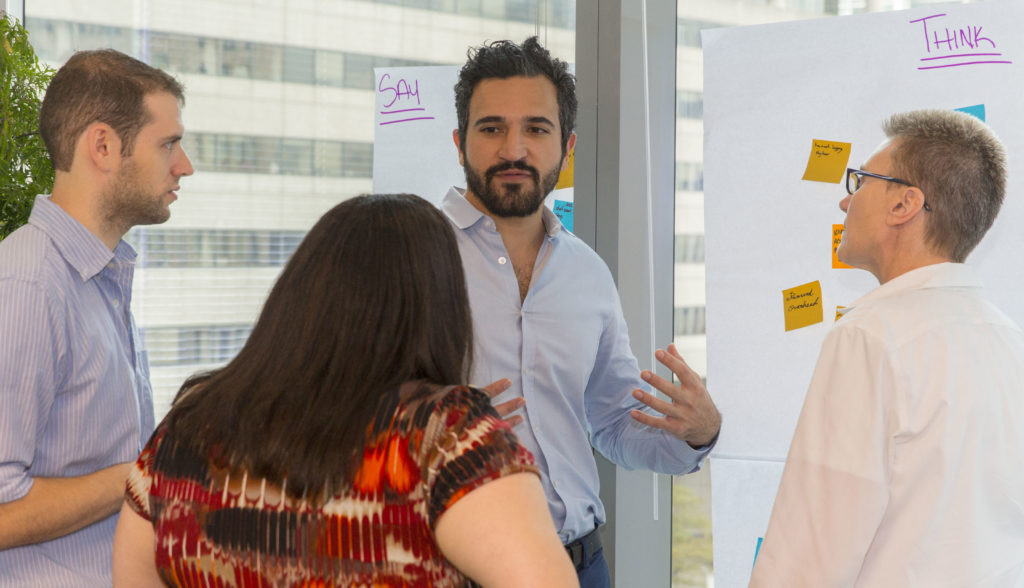 People at a white board going through a facilitated activity