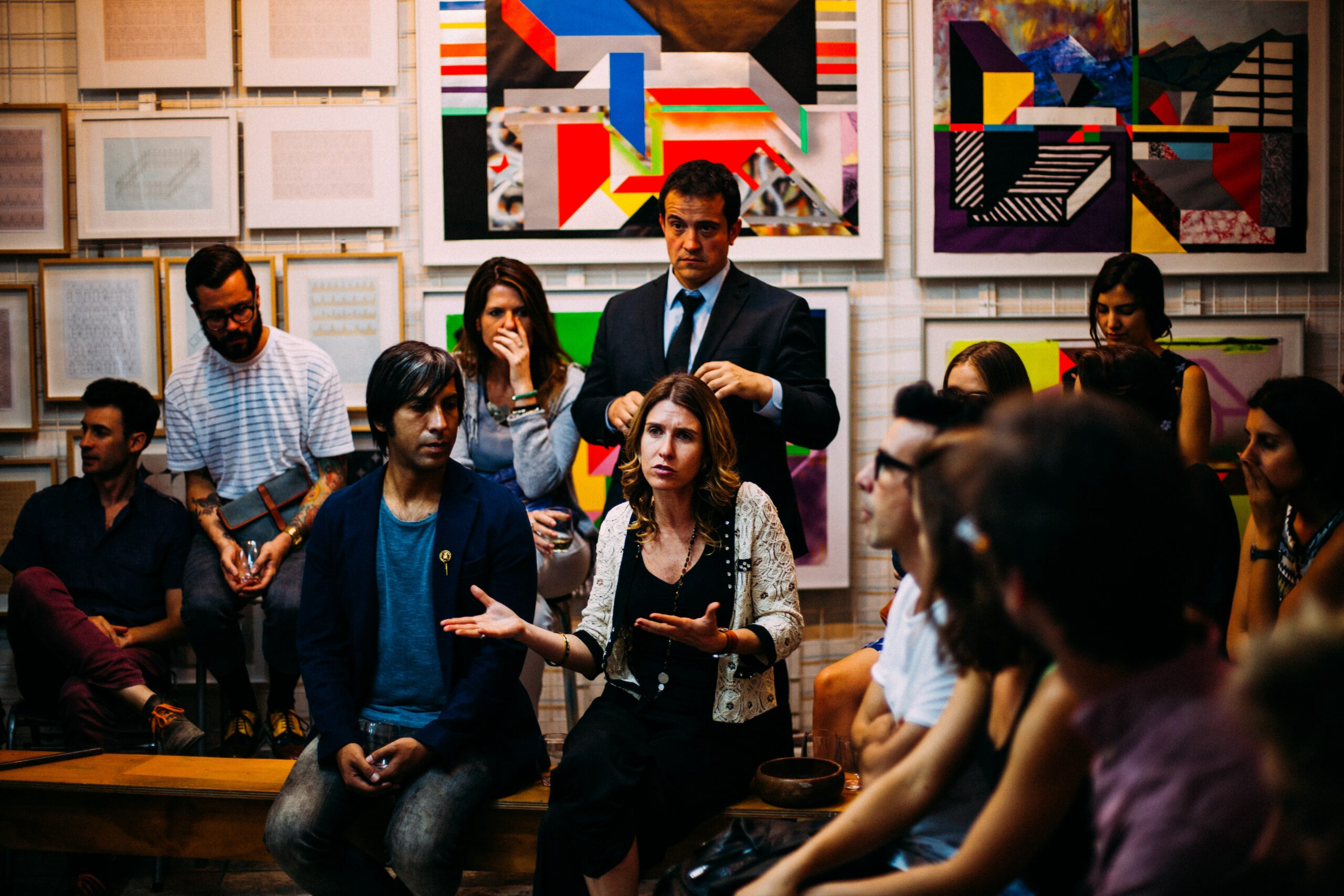 A group of young, diverse people, some sitting and some standing, having a serious group conversation