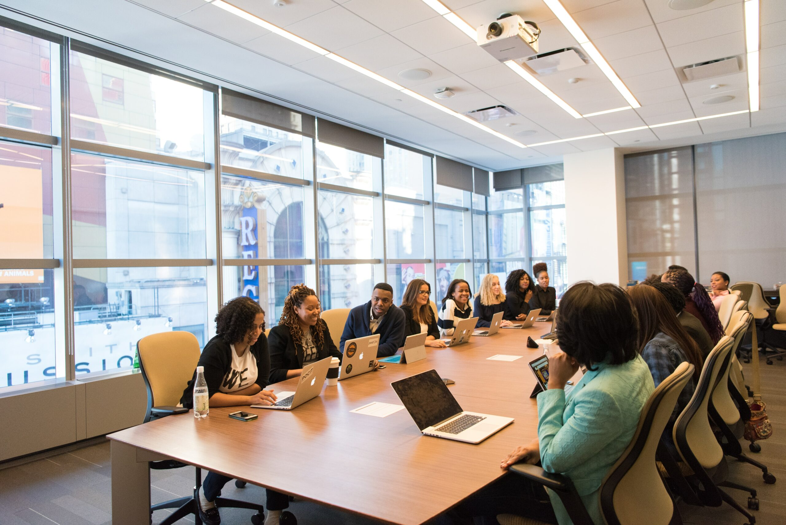 Coworkers seated around a long wooden conference table in a windowed conference room